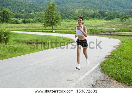 Beautiful Asian woman running on country road.