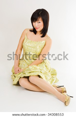 beautiful asian woman sitting in gold evening gown - stock photo