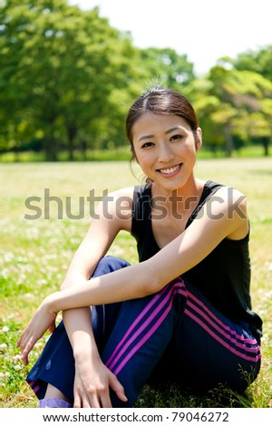 beautiful asian woman sitting in the park - stock photo