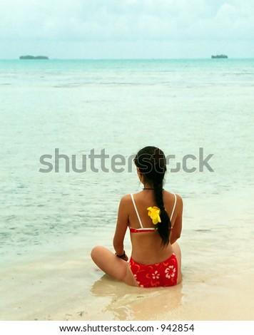Beautiful asian woman sitting on a Polynesian beach in Tahiti. - stock photo