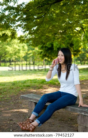 beautiful asian woman sitting on the park bench - stock photo