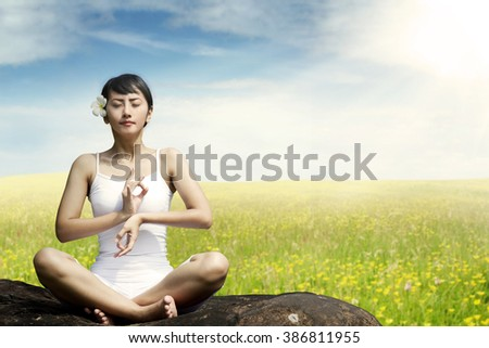 Beautiful Asian woman sitting on the rock while meditating at the meadow in springtime - stock photo