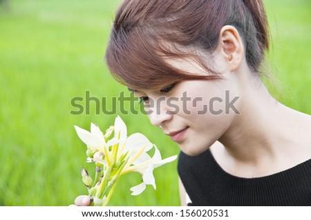 Beautiful Asian woman smelling canna flower. - stock photo