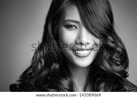 Beautiful Asian woman smiling in a black and white photo. - stock photo