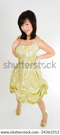 Beautiful asian woman standing in gold dress with amzing smile - stock photo