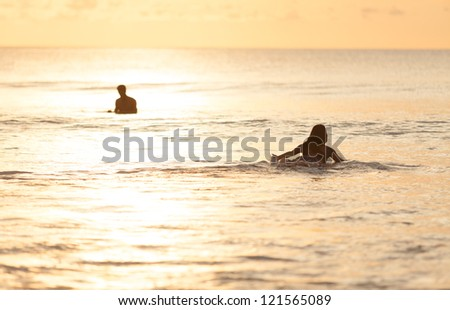 Beautiful asian woman swimming on surfboard - stock photo