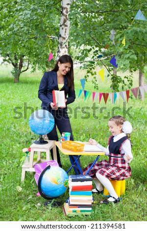 Beautiful asian woman teacher mother talking reading book to schoolgirl outdoors, back to school - stock photo