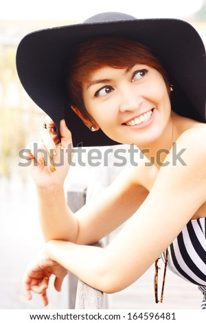 Beautiful Asian woman touches her black hat and look up - stock photo