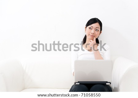 beautiful asian woman using laptop computer on the sofa - stock photo