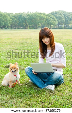 beautiful asian woman using laptop computer with dong in the park - stock photo