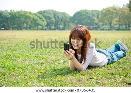 beautiful asian woman using smart phone in the park - stock photo