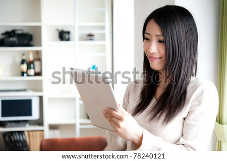 beautiful asian woman using tablet computer - stock photo
