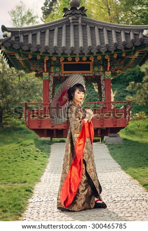 Beautiful asian woman walking in the garden and wearing traditional japanese kimono and red umbrella  - stock photo
