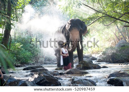 Beautiful Asian Woman wears thai or Lanna dress with her elephant