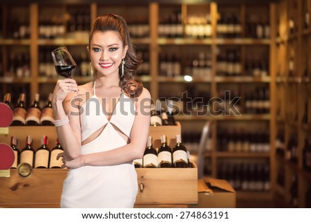 Beautiful asian woman with a glass of wine - stock photo