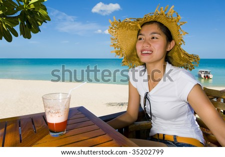 beautiful asian woman with cocktail at the beach - stock photo