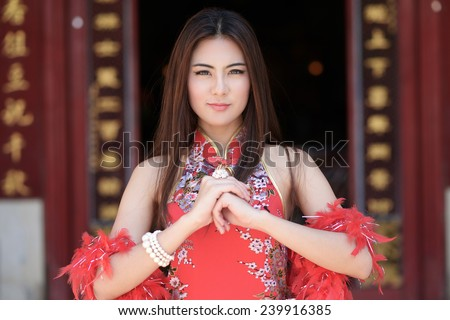 Beautiful asian woman with congratulate gesture in Chinese New Year - stock photo