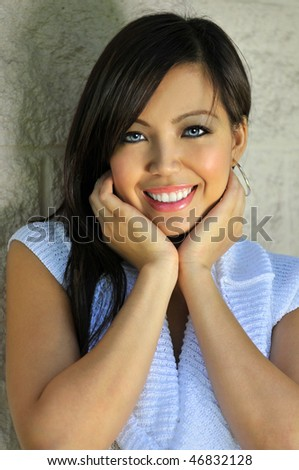 Beautiful Asian woman with hands on face over textured wall