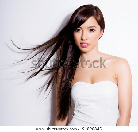 beautiful asian woman with long hair posing on grey background - stock photo