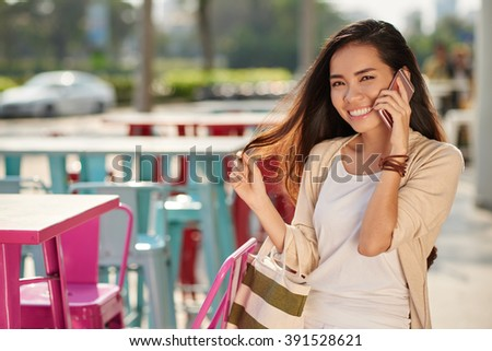 Beautiful Asian woman with long hair talking on the phone and looking at camera