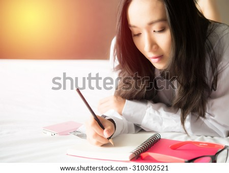 Beautiful asian woman writing notes lying on bed - stock photo