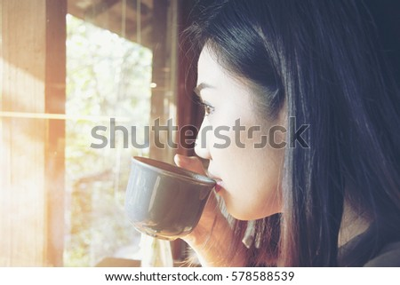 beautiful asian women drink hot coffee or tea in morning at her home.