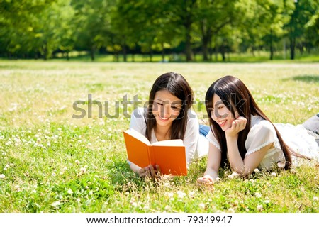 beautiful asian women reading a book in the park - stock photo