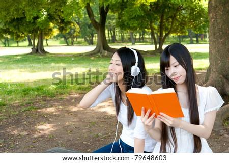 beautiful asian women relaxing in the park - stock photo