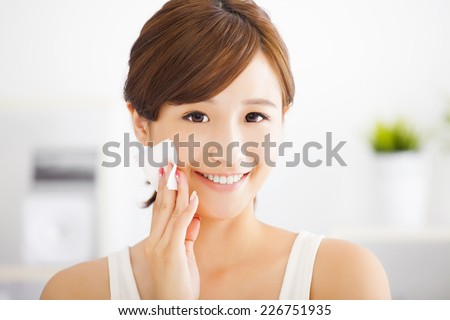 Beautiful asian young woman cleaning her face with cotton - stock photo