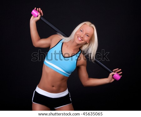 Beautiful  athlete doing exercise with fit bar - stock photo