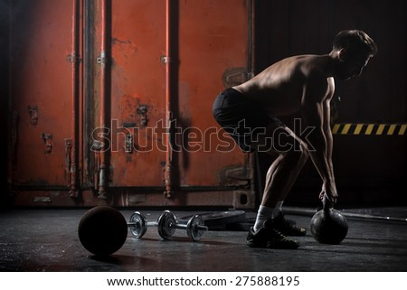 Beautiful athlete doing kettlebell swings. View from the back. Athlete bare-chested. Studio shot in a dark tone. - stock photo