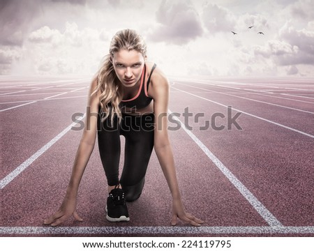 Beautiful athlete on a race track is ready to run - stock photo