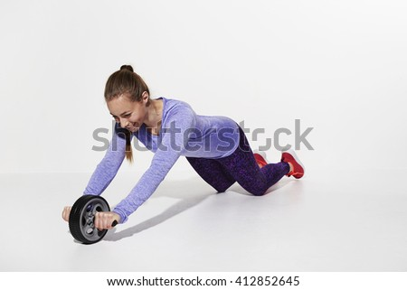 Beautiful athlete stretching with gym wheel