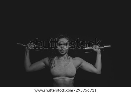 Beautiful athlete with dumbbells on a black background.