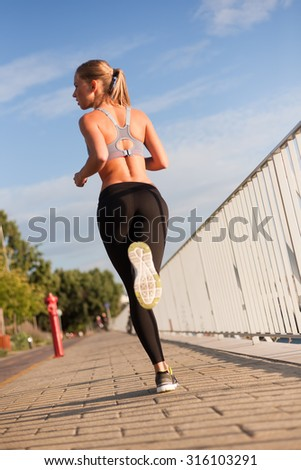 Beautiful athletic blond woman's late afternoon workout in urban setting.