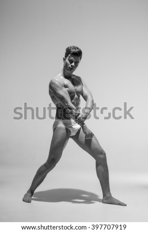 Beautiful athletic bodybuilder male model posing in studio. Muscular healthy sexy body. Expression on camera. Nude natural.