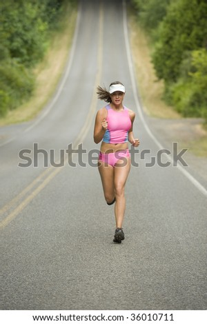 Beautiful, athletic female caucasian runner on a hilly country road. Vertically framed shot. - stock photo