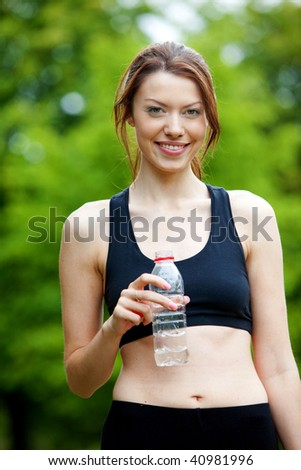 Beautiful athletic female outdoors with a bottle of water - stock photo