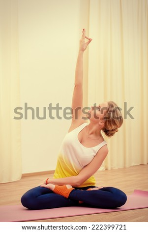 Beautiful athletic girl doing yoga exercises indoor. Lotus pose. Meditation. - stock photo