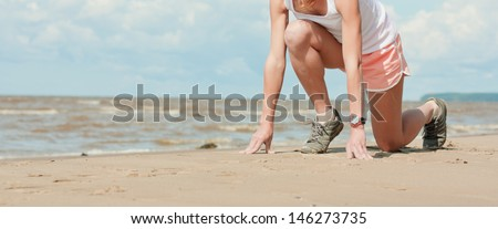 Beautiful athletic girl in a starting position on the beach.