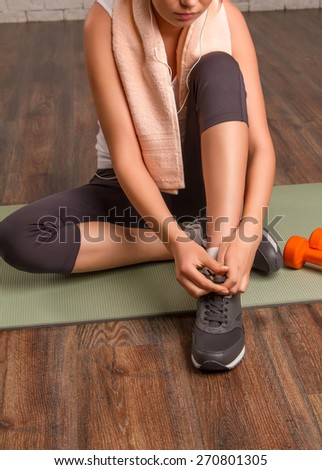 Beautiful athletic girl tying shoelaces, sitting on a mat. close-up - stock photo