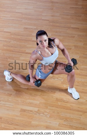 Beautiful athletic trainer shows examples of exercises in the gym