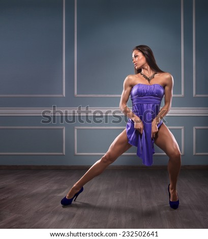 Beautiful athletic woman in a blue dress posing in studio - stock photo