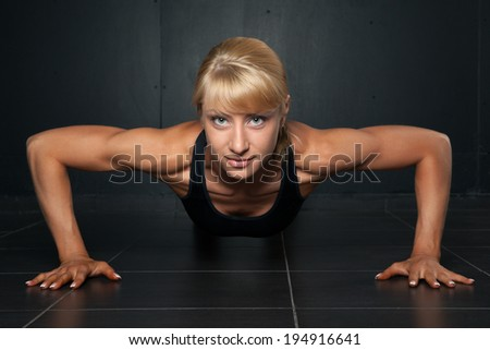Beautiful athletic woman is pushed up on  a dark background - stock photo