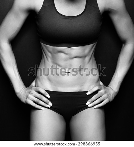 Beautiful athletic woman shakes her abdominal muscles on dark background - stock photo