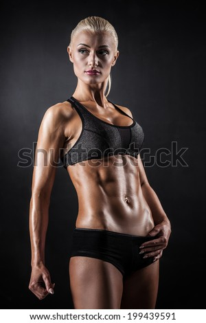 Beautiful athletic woman showing muscles on dark background - stock photo