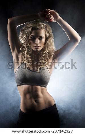 Beautiful athletic woman showing muscles on smoke  - stock photo