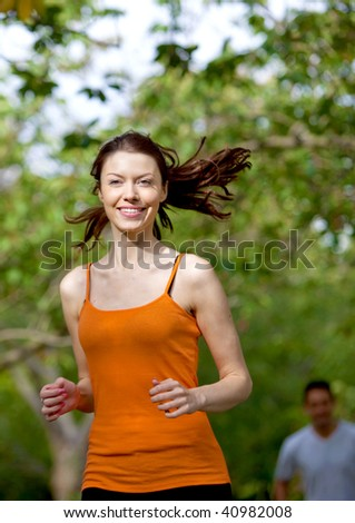 Beautiful athletic woman smiling and running outdoors - stock photo