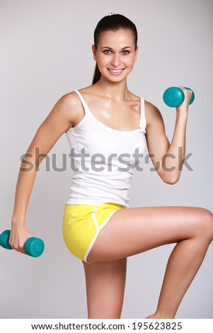 Beautiful athletic woman working out with dumbbells on gray background