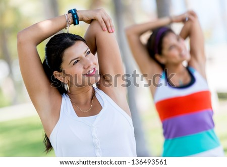Beautiful athletic women stretching at the park - stock photo